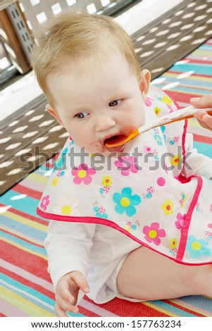 Little baby girl feeding with a spoon in outdoors. - stock photo