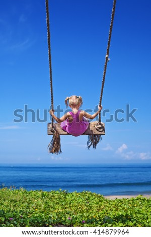 Little baby girl fly high with fun on rope swing on blue sky background on sea beach with waves and surf in tropical island. Travel lifestyle, people activity on summer family vacation with child. - stock photo