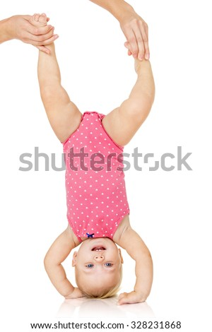 Little baby girl hanging upside down, isolated on white - stock photo
