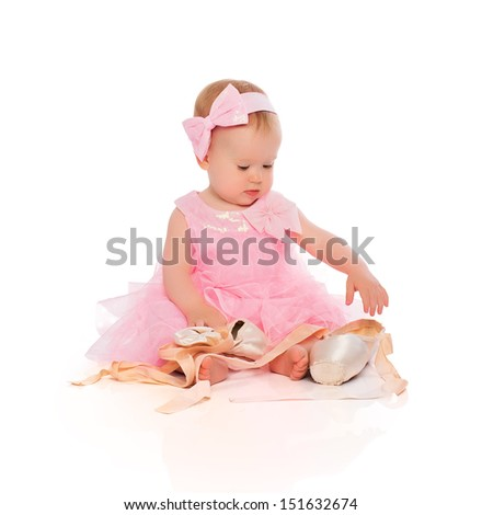 Little baby girl in a pink ballerina dress with pointe shoes isolated on a white background - stock photo