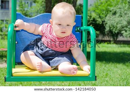 little baby girl in a striped dress sitting on a swing and looks  with interest - stock photo