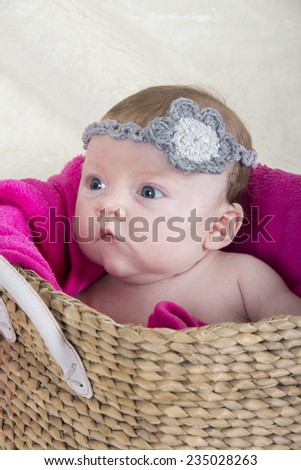 little baby girl in basket with accessory on her head