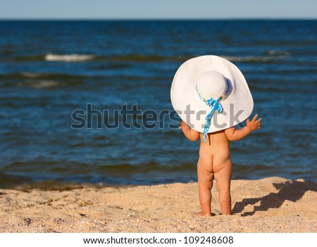 Little baby girl in big hat on the beach looking at sea - stock photo
