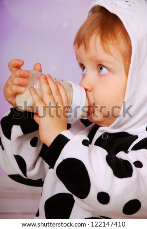 little baby girl in cow costume drinking milk from bottle - stock photo