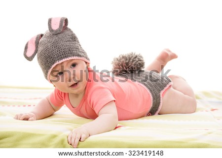 Little baby girl in croched bunny costume laying and looking away