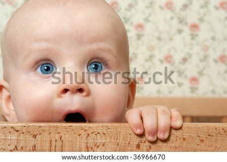Little baby girl in her bed - stock photo