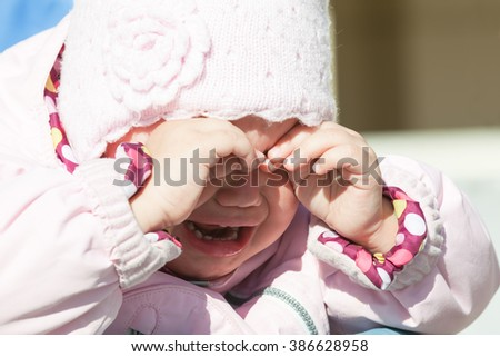 Little baby girl in pink clothes crying, closeup outdoor portrait - stock photo