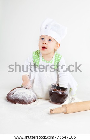 Little baby girl in the cook costume sitting near bread and pot of flour.