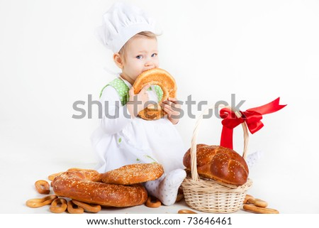 Little baby girl in the cook costume sitting near bread rolls and bagels. She is eating bagel.