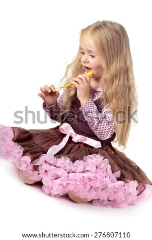 Little baby girl in tutu skirt playing with party blower isolated on a white background - stock photo