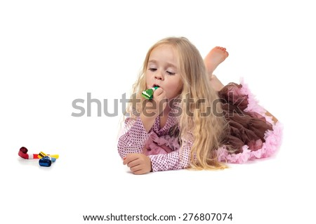 Little baby girl in tutu skirt using party blower isolated on a white background - stock photo