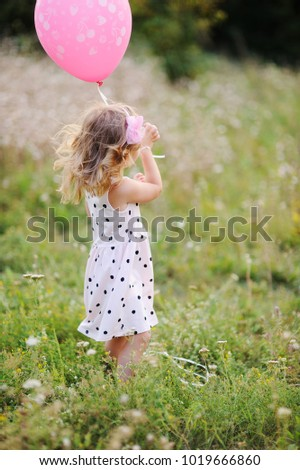 little baby girl in white dress with pink air balloon on a background of greenery, grass at sunset.
