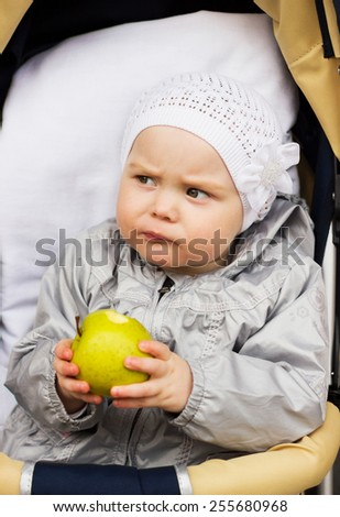 Little baby girl is eating apple - stock photo