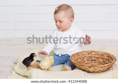 Little baby girl is playing with chicks