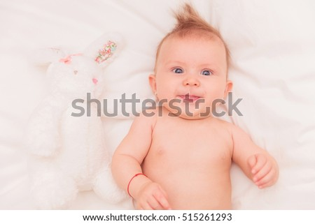 little baby girl laughing near toy bunny while lying on her bed