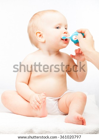 Little baby girl learning to brush teeth with mother's help