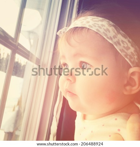 Little baby girl looking out window - With Instagram effect - stock photo