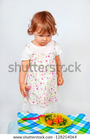 little baby girl looking sadly on a plate with  broccoli and carrot - stock photo
