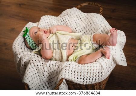 little baby girl lying in a wicker basket - stock photo