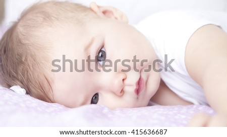 Little baby girl on  a bed preparing for a nap