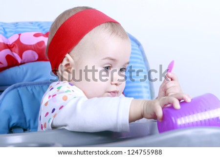 Little baby girl on high chair