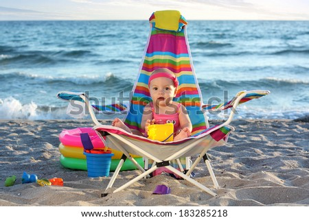 Little baby girl on the sand beach with toys - stock photo