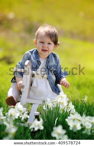 Little baby girl on wooden rocking horse - stock photo