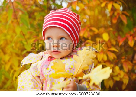 little baby girl outdoors discovers autumn leaves