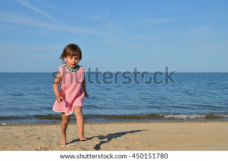 Little baby-girl playing on the beach
