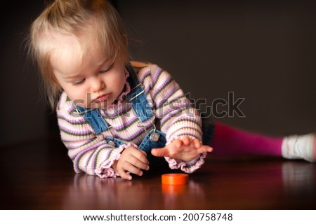 Little baby girl playing with a block - stock photo