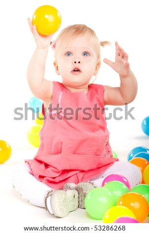 Little baby girl playing with balls isolated on white
