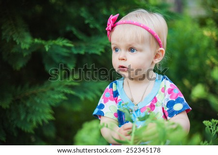 little baby girl playing with flowers in the park or garden - stock photo
