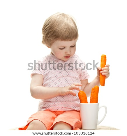 Little baby girl playing with fresh carrots isolated on white - stock photo
