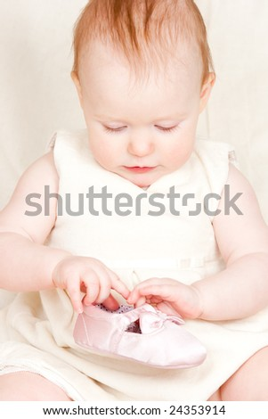 Little baby girl playing with shoe
