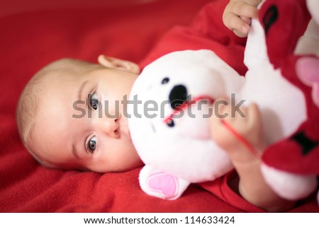 Little baby girl playing with teddy bear - stock photo