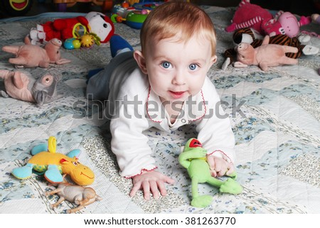 little baby girl playing with toys on the floor in children's room - stock photo