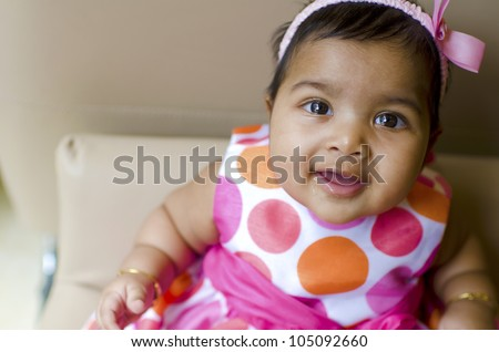 little baby girl resting on the arm of sofa seat, shallow dof, focus on eyes - stock photo