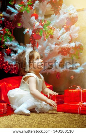 Little baby girl sit under the Christmas tree with a lot of gifts. Christmas mood. New Year. - stock photo