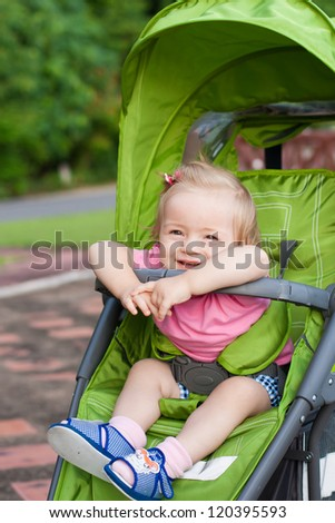Little baby girl sitting in a baby buggy