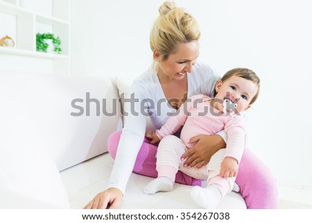Little baby girl sitting with smiling mother on the sofa .Shallow doff - stock photo