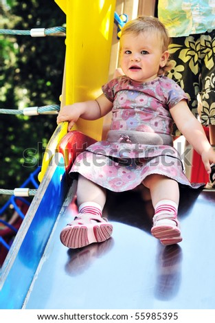Little baby girl sliding on playground in the park