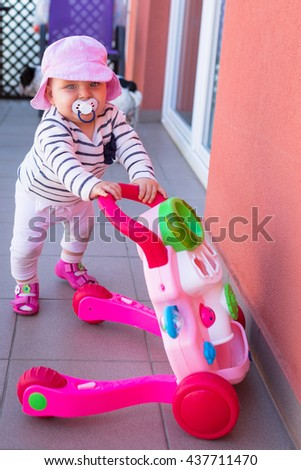 Little baby girl walking with the baby pusher - stock photo