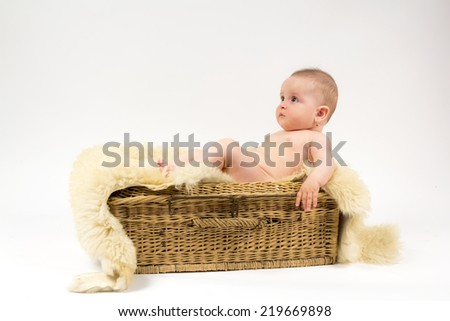 Little baby girl with a wicker basket and a wool blanket