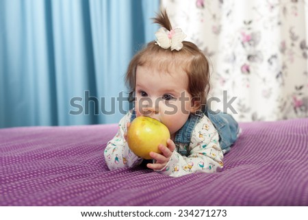 Little baby girl with an apple smiling indoors