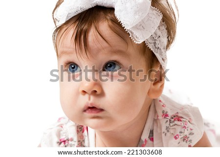 Little baby girl with blue eyes and with fillet on her head closeup surprised face isolated on white background - stock photo