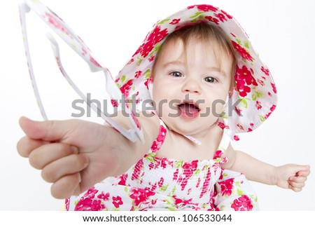 Little baby girl with pretty red flower dress and hat handing over her sun glasses to you. - stock photo