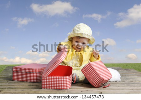 little baby girl with red and white vintage suitcases, outdoors