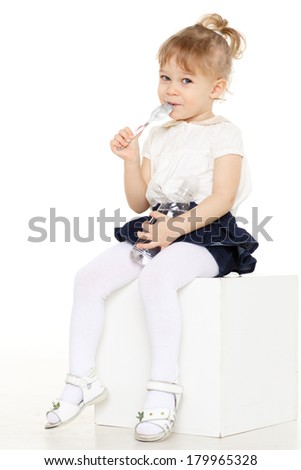 Little baby girl with spoon eats yogurt on a white background. - stock photo