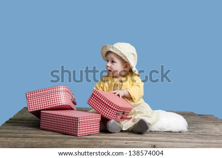 little baby girl with vintage suitcases on an old wooden floor, isolated on blue - stock photo