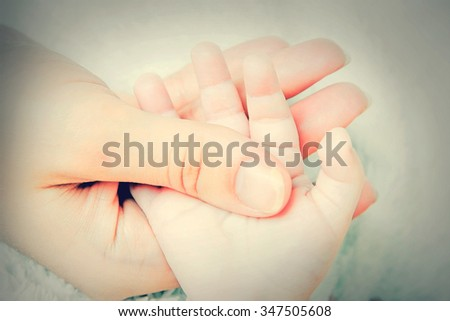 Little baby hand in mother's hand - stock photo